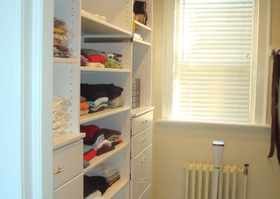 White melamine master closet with drawers, laundry hamper, fully adjustable shelves and rods.