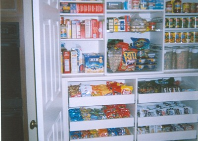 Wall pantry in white melamine. Deep pull-outs at bottom allow access to items in the back.